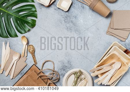 Eco Craft Paper And Wooden Tableware. Paper Cups, Dishes, Bag, Plates And Bamboo Cutlery On Gray Bac