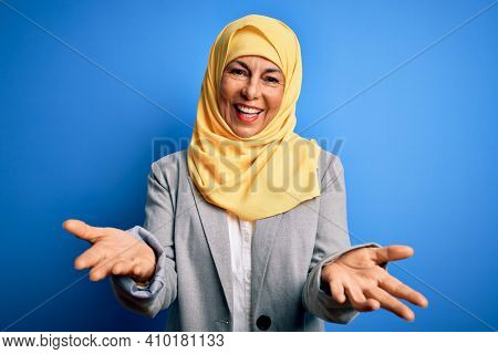 Middle age brunette business woman wearing muslim traditional hijab over blue background smiling cheerful offering hands giving assistance and acceptance.