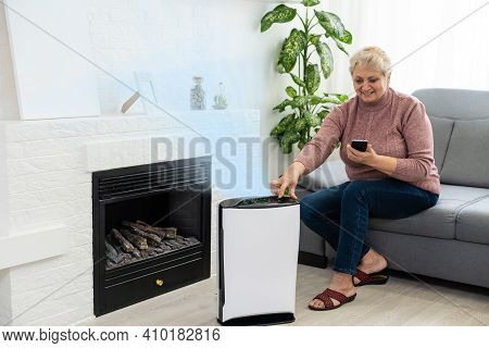 Elderly Woman Next To An Air Purifier Moving To A New Apartment