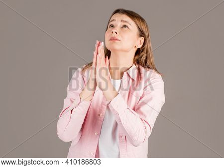 Gloomy Dissatisfied Woman Keeps Palms In Prayer Gesture, Feels Sorry For Making Mistake, Asks For Fo