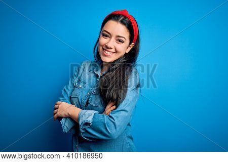 Young brunette woman wearing casual denim shirt over blue isolated background happy face smiling with crossed arms looking at the camera. Positive person.