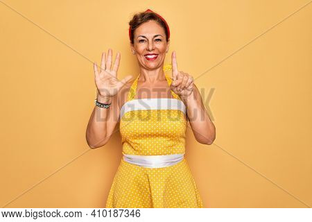 Middle age senior pin up woman wearing 50s style retro dress over yellow background showing and pointing up with fingers number six while smiling confident and happy.