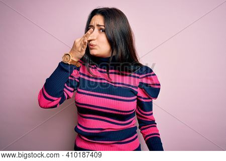 Young brunette elegant woman wearing striped shirt over pink isolated background smelling something stinky and disgusting, intolerable smell, holding breath with fingers on nose. Bad smell