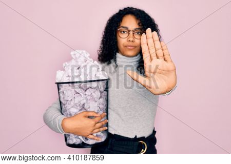 Young african american woman wearing glasses holding wastebasket with cumpled papers with open hand doing stop sign with serious and confident expression, defense gesture