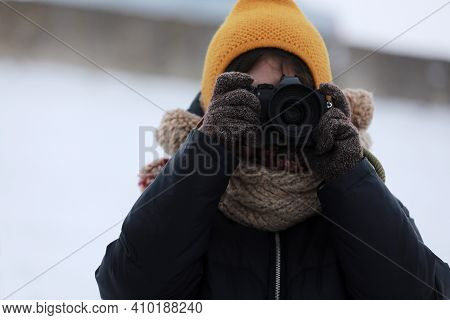 Portrait Of A Little Girl And Holding Camera In Park. Little Girl Photographer In Winter. Young Phot