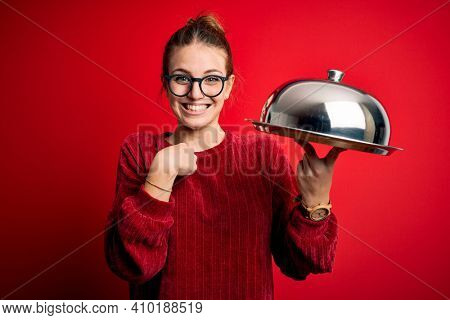 Young beautiful redhead woman holding waitress tray over isolated red background with surprise face pointing finger to himself