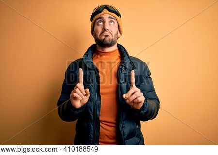 Young handsome skier man with beard wearing snow sportswear and ski goggles Pointing up looking sad and upset, indicating direction with fingers, unhappy and depressed.