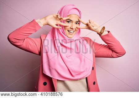 Young beautiful girl wearing muslim hijab standing over isolated pink background Doing peace symbol with fingers over face, smiling cheerful showing victory