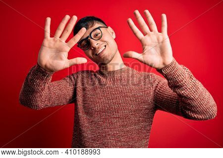 Young handsome hispanic man wearing nerd glasses over red background showing and pointing up with fingers number ten while smiling confident and happy.