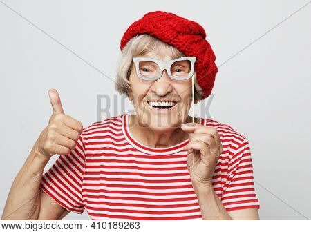 lifestyle, emotion  and people concept: funny grandmother with fake glasses, laughs and ready for party, over grey background