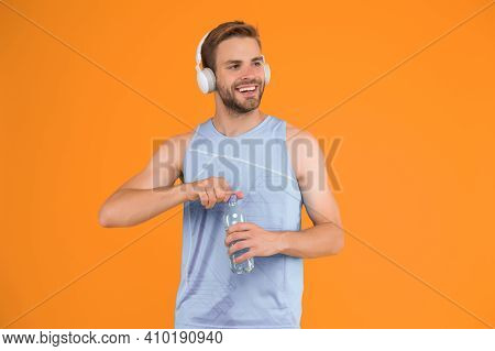 Celebrating Health. Healthy Man Open Water Bottle. Fitness Coach Wear Headphones. Water And Hydratio