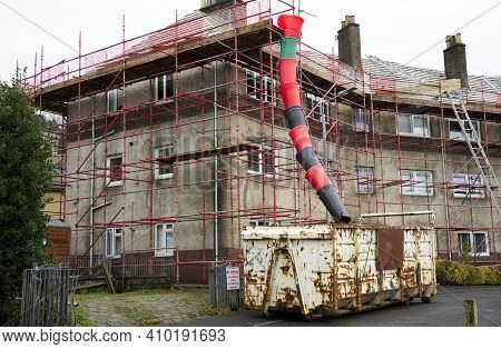 House Renovation Work With Skip And Rubbish Chute