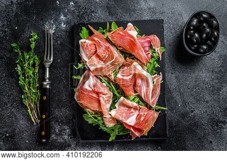 Sliced Jamon Serrano Pork Ham Meat On A Marble Board. Black Background. Top View