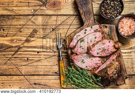 Rare Slices Of Roast Beef Sirloin Tri Tip Steak Bbq On A Wooden Cutting Board. Wooden Background. To