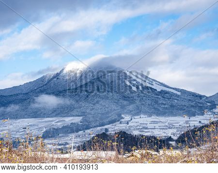 The Snow Covered Forests On The Side Of Mt. Kosha With Clouds Around The Summit As Seen From Yamanou