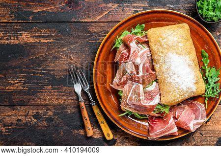 Spanish Bocadillo De Jamon, Serrano Ham Sandwich On Ciabatta Bread With Arugula. Dark Wooden Backgro