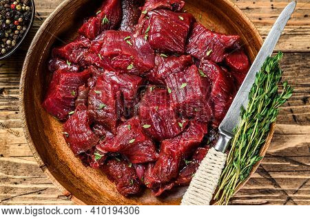 Raw Cut Wild Venison Meat For A Goulash In A Wooden Plate. Wooden Background. Top View