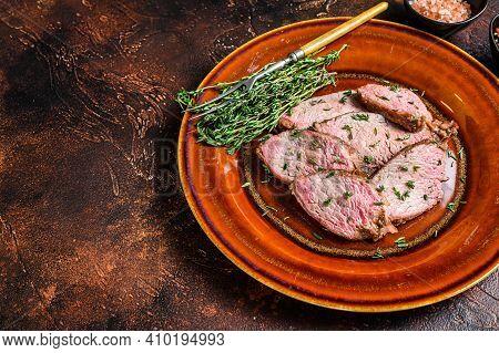 Sliced Roast Beef Sirloin Tender Steak On A Rustic Plate. Dark Background. Top View. Copy Space