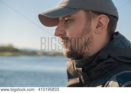 Side View Of Aserious Confident Bearded Man In Baseball Cap Looking Into The Distance On The Backgro