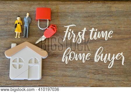 Toy House, Keys, Padlock And People Miniatures Over Wooden Background Written With First Time Home B