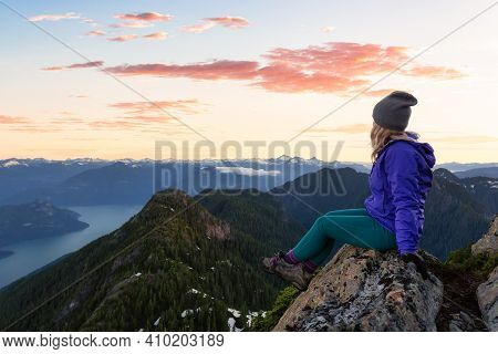 Adventurous Woman Hiking On The Rocky Peaks Of The Mountains. Colorful Sunrise Sky Art Render. Taken