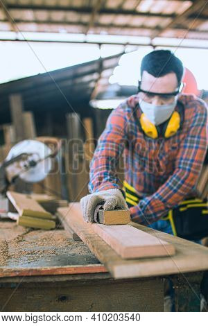 Carpenter Is Working In A Woodworking Office.caucasion White Carpenter Using Sandpaper To Polish The