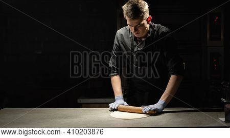A Chef In A Suit Rolls Out Thin Pizza Dough On A Table In A Pizzeria Next To A Place For Text. Banne