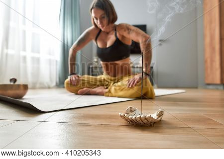 Healthy Young Woman Doing Uddiyana Bandha Abdominal Lock While Sitting On Floor Mat Beside Burning S