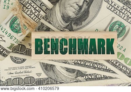 Business And Finance Concept. On The Dollars Is A Wooden Plate With The Inscription - Benchmark