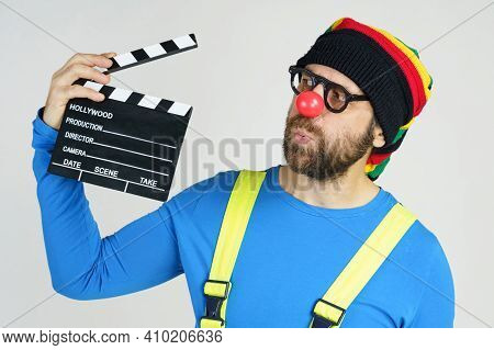 Humor And Fun Concept. A Clown In A Bright Suit Holds A Movie Clapperboard In His Hands.