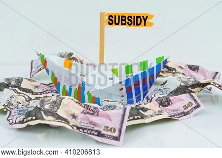 Business And Finance Concept. A Paper Boat From A Business Graph Floats On A Sea Of Money. The Text