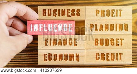 Business And Finance Concept. From A Set Of Wooden Blocks With Financial Inscriptions, A Hand Takes