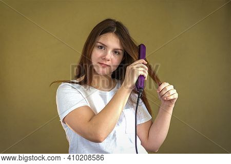 A 14-15 Year Old Girl Straightens Her Long Dark Hair With A Hair Straightener. Selective Focus.