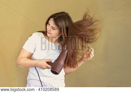 A 14-15 Year Old Girl Dries Her Long Dark Hair With A Hair Dryer. Selective Focus.