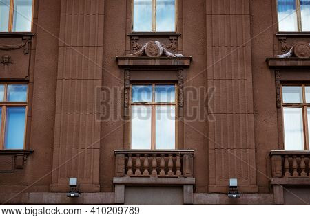 The Facade Of The Building With Windows And Balusters, The Sky Is Reflected In The Windows