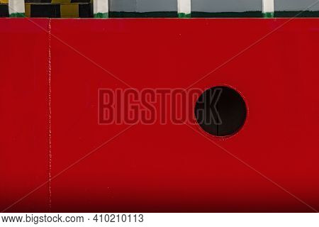 Red Metal Background With Black Circle Window.  Porthole At Ship Board.  Empty Place For Text, Copy