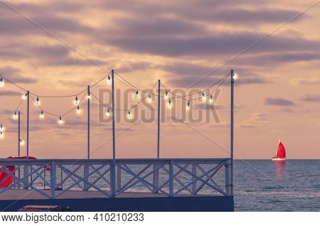 Romantic Pier At Sunset With Glowing Bulbs, Side View. A Yacht With A Red Sail Is On The Horizon.