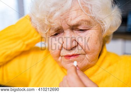 Elderly Woman Taking Pill At Home In The Kitchen