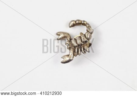 A Closeup Of An Old Silver Scorpion. Jewelry In The Form Of An Arthropod On A White Background. Jewe