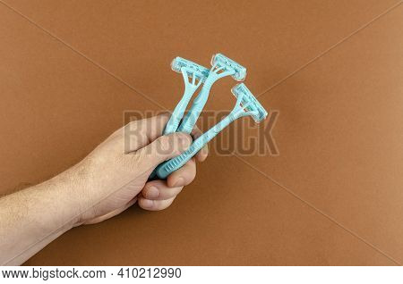 Handholds Light Blue Plastic Razors On A Brown Background. Three New Unisex Razors In A Man's Hand.