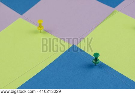 Two Pushpins And Many Colorful Sticky Notes. Green And Yellow Pushpins On A Multicolored Background.