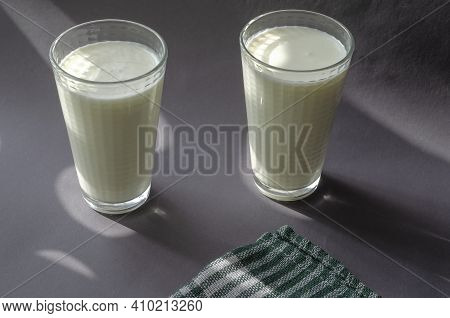 Two Glasses Of Kefir On A Gray Surface With Shadows. Full Glasses And A White And Green Napkin With