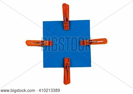 Abstract Geometric Composition Of Brown Plastic Clothespins And Blue Square Sheet Of Paper On White