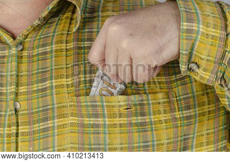 An Adult Man In A Green And Yellow Plaid Shirt Pulls Money Out Of His Breast Pocket. Male Hand With