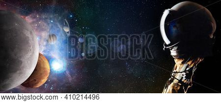 Concept Of An Astronaut Looking Up Into The Stars And Solar System Planets. Sci-fi Space Exploration