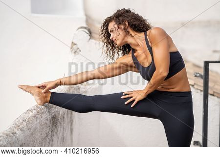Middle-aged Woman With Fitness Body Working Out On The Terrace Of Her House