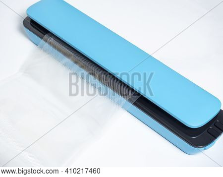 Close-up Of A Blue Vacuum Packer Isolated On A Bright Blue Background. The Package Is Inserted Into