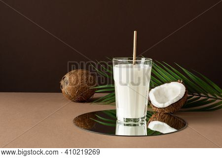 Modern Still Life Of Coconut Vegan Milk With Halves Of Nuts Over Brown Background.