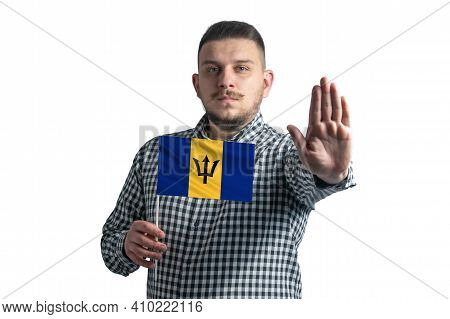 White Guy Holding A Flag Of Barbados And With A Serious Face Shows A Hand Stop Sign Isolated On A Wh
