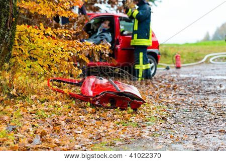 Accident - Fire brigade rescues accident Victim of a car, a car door lying on the slippery pavement, Focus on car door